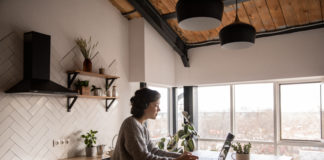 young woman surfing laptop in kitchen 4049990 scaled